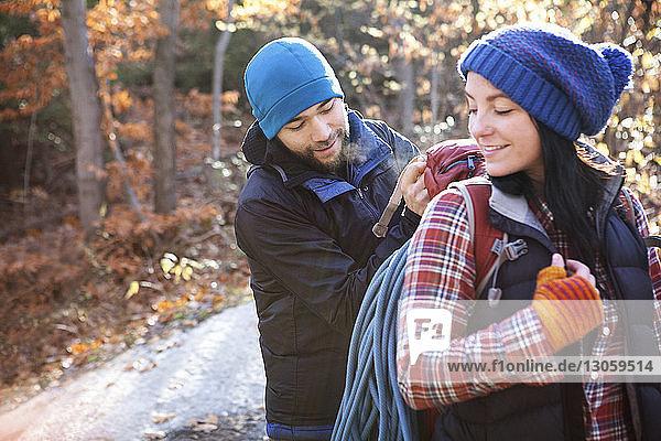 Mann assistiert seiner Freundin beim Rucksack tragen  während er auf dem Spielfeld steht