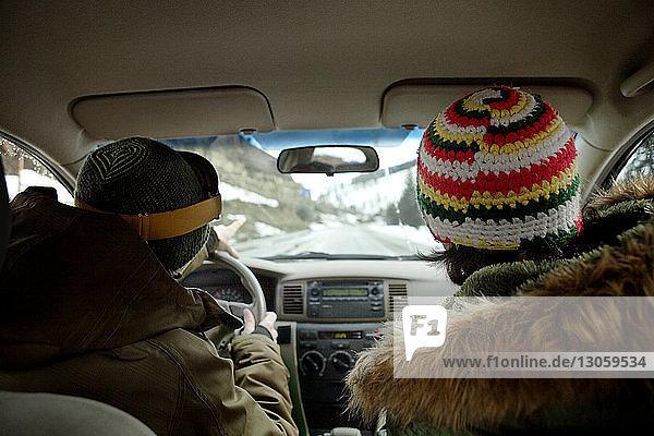 Rückansicht der im Auto sitzenden Freunde