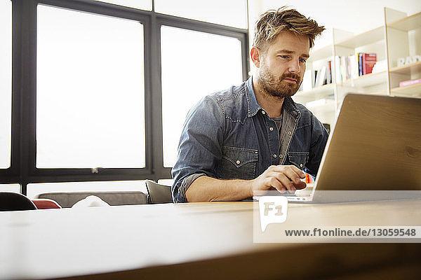 Mann benutzt Laptop zu Hause