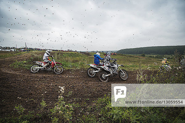 Men riding dirt bikes on field during competition