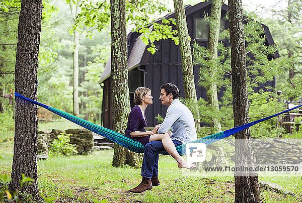 Couple talking while sitting on hammock