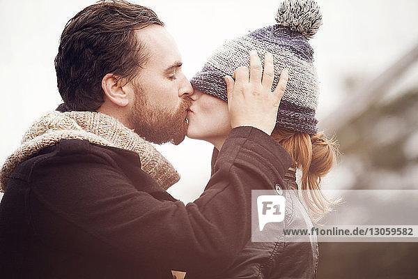 Seitenansicht eines Paares  das sich bei klarem Himmel küsst