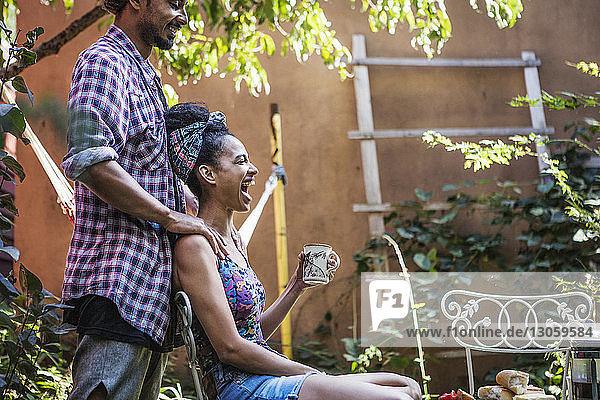 Mann steht mit Händen auf der Schulter der Frau und sitzt auf einem Stuhl im Rasen