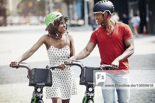 Lächelndes Paar mit Fahrrädern zu Fuß auf der Straße in der Stadt