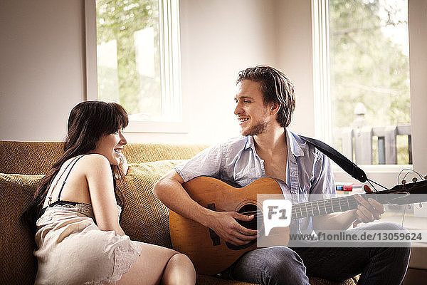 Man playing guitar while sitting with girlfriend on sofa at home