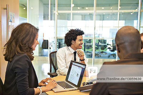 Businesswoman using laptop by colleagues in meeting