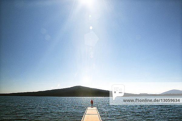 Distanzansicht eines Wanderers  der auf einer Promenade steht  die in Richtung Meer gegen den Himmel führt