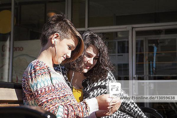 Freunde benutzen Mobiltelefon  während sie auf einer Bank sitzen