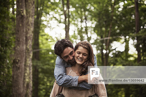 Happy woman piggybacking man while walking in forest