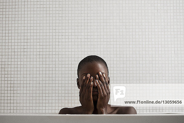 Woman with hands covering eyes in bathroom at home