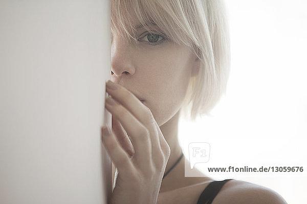 Porträt einer Frau  die sich zu Hause hinter einer weißen Wand versteckt