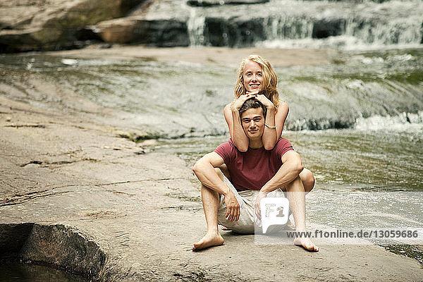 Porträt eines auf Felsen sitzenden Paares am Flussufer