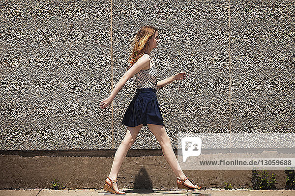 Seitenansicht einer Frau,  die auf einem Fußweg geht