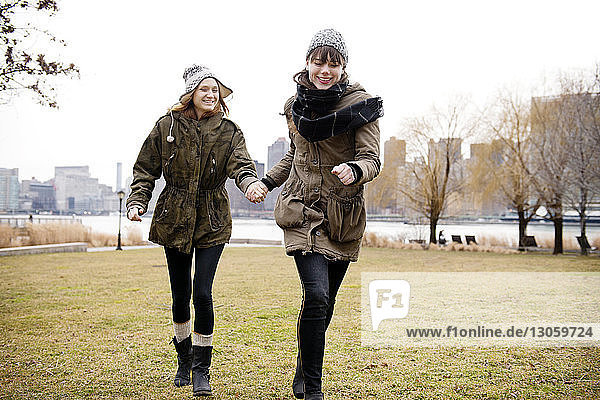 Smiling female friends holding hands and walking on grassy field