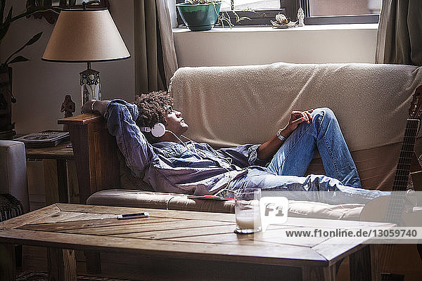 Man listening music while relaxing on sofa at home
