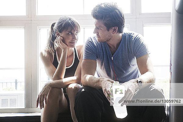 Frau schaut den Mann an  während sie im Fitnessstudio sitzt