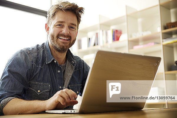 Portrait of happy man using laptop at home