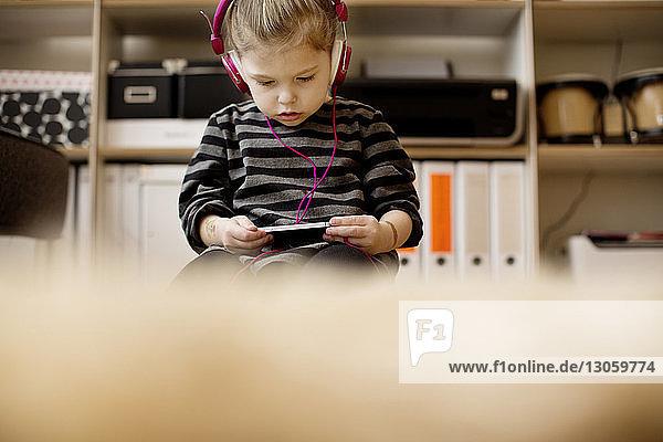 Mädchen hört Musik  während sie zu Hause telefoniert