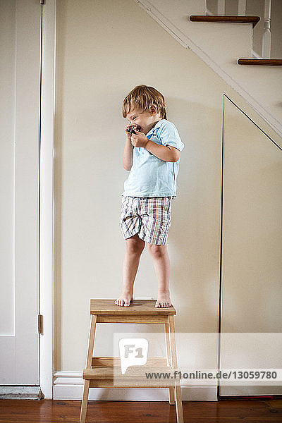 Happy boy standing on stool at home