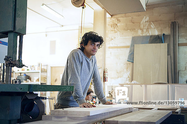 Thoughtful carpenter standing at workbench