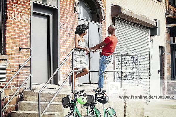 An einem Geländer gegen Gebäude stehendes Ehepaar