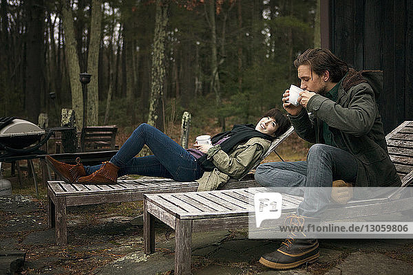 Frau sieht Mann beim Kaffeetrinken an  während sie auf einem Liegestuhl sitzt