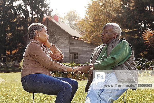 Romantisches älteres Paar  das im Hinterhof sitzend Händchen hält
