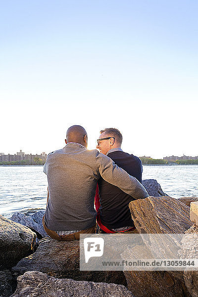 Rear view of happy man sitting arm around with boyfriend on rocks at East River against clear sky