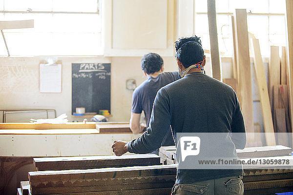 Rückansicht der in der Werkstatt arbeitenden männlichen Schreiner