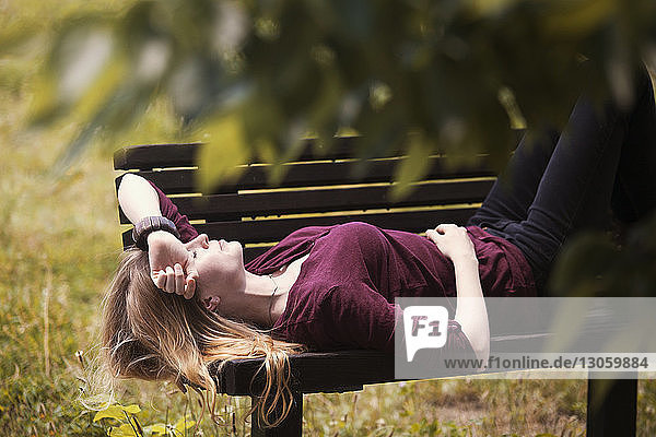 Woman relaxing on bench at park