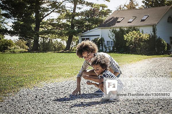 Glückliche Geschwister sammeln Steine im Hinterhof