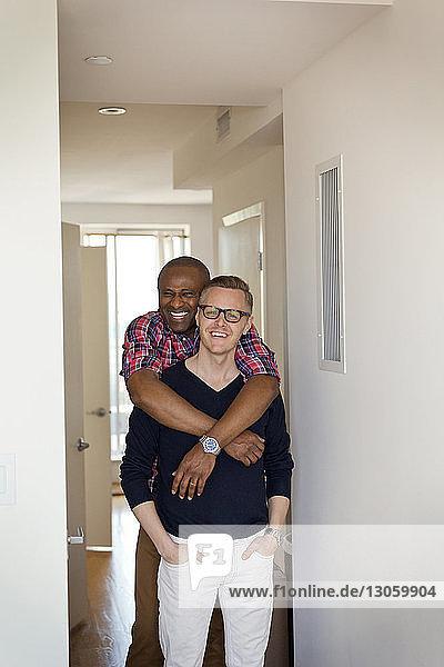 Porträt eines glücklichen Mannes  der seinen Freund umarmt  während er zu Hause im Flur steht