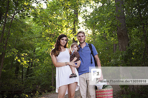 Low angle portrait view of family standing in forest