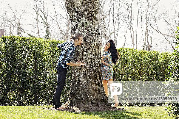 Ehepaar steht um einen Baum im Rasen