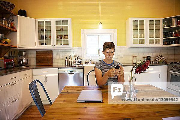 Weibliche Textnachrichten  während sie in der Küche am Tisch sitzen