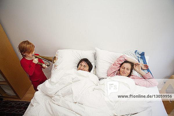 Junge spielt Trompete  während die Eltern zu Hause im Bett schlafen