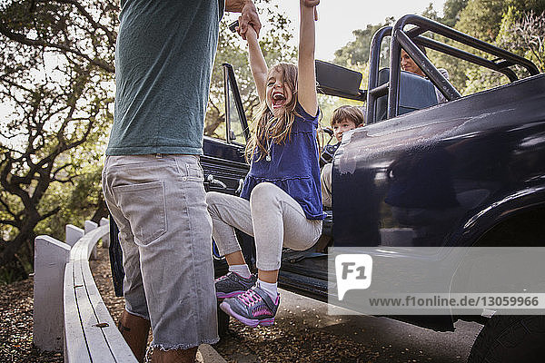 Vater schwingt Tochter  während die Familie im Geländewagen sitzt