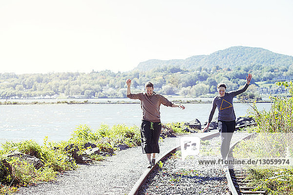 Friends balancing on railroad track against clear sky
