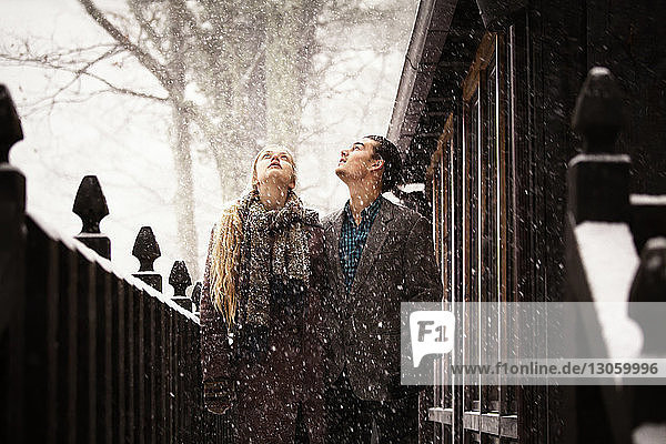 Couple looking up while standing by fence during winter
