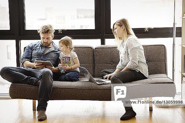 Familie nutzt Technologien  während sie zu Hause auf dem Sofa sitzt