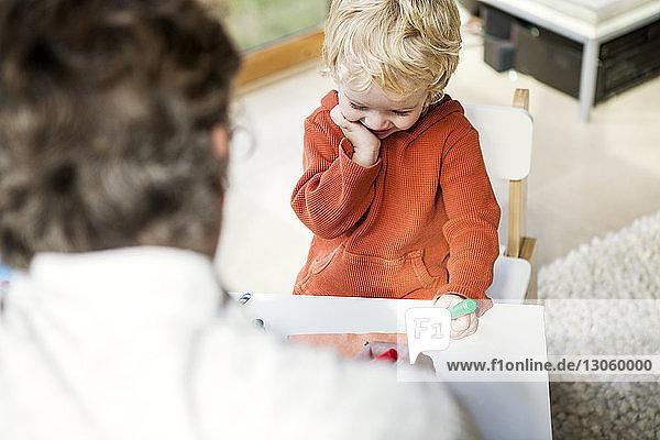 Schrägaufnahme eines Vaters  der seinem Sohn das Schreiben beibringt  während er zu Hause auf einem Stuhl sitzt