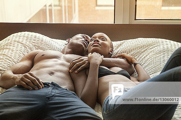 Couple relaxing on bed at home