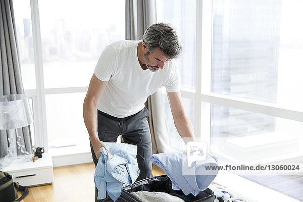 Mann wählt Hemden aus  während er während einer Geschäftsreise im Hotelzimmer steht