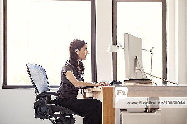 Seitenansicht einer Frau  die im Büro am Computer arbeitet
