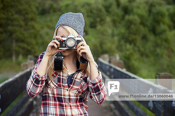 Woman photographing with camera while standing on bridge