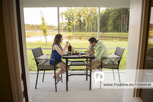 Couple having food while sitting at table