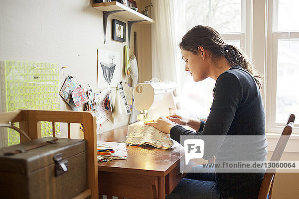 Side view of woman using sewing machine at home