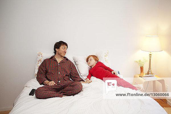 Vater und Sohn halten sich an den Händen  während sie zu Hause auf dem Bett sitzen