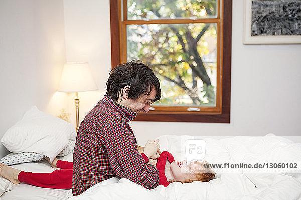 Mann spielt mit Sohn auf Bett im Schlafzimmer