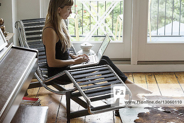 Woman using laptop while sitting on lounge chair at home